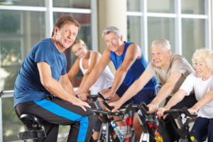 Man as fitness instructor in gym exercising with senior group in spinning class