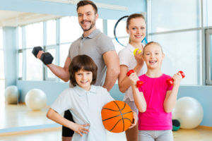Happy family holding different sports equipment while standing close to each other in health club