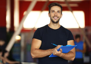 Portrait of personal trainer holding clipboard with training plan in gym