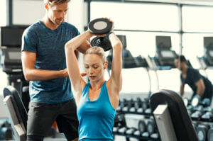 Trainer helping athletic woman at gym. Personal trainer giving weightlifting training to girl in gym. Young woman working out at gym using dumbbells with help of personal trainer.